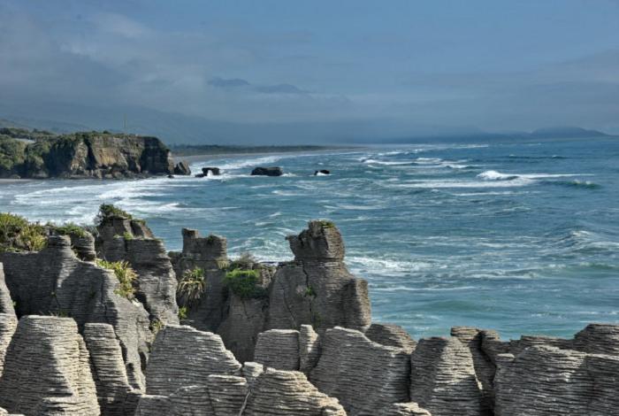 """千层岩,属于海洋沉积结""""千层岩""""是岸边一组巨大的岩体,层层堆砌,状似层层巨型的煎饼,故又称""""煎饼岩""""。它属于海洋沉积结晶白云岩,石质坚硬致密。纹理成层状结构,在层与层之间夹一层浅灰岩石,石纹成横向,外形似久经风雨侵蚀的岩层。有人形象地称它为""""大自然的年轮""""。"""