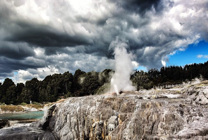 """普胡图间歇泉是南半球最大的活跃间歇喷泉,坐落于被誉为间歇泉台地的泉华岩台之上。这个举世闻名的间歇泉""""脾气火爆"""",是罗托鲁瓦地区最受游客青睐的拍照景点之一。喷出的泉水炽热沸腾,有浓重的硫磺味,而且撒在身上有泥点。泉眼喷发时能量巨大,整个景区雾气重重。"""