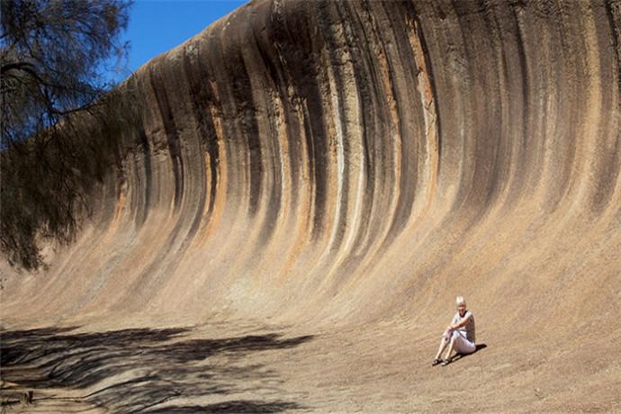 """波浪岩是澳大利亚的一种巨大岩层,位于西部谷物生长区边缘的海登城附近。这个向外伸悬的岩体之所以被称为波浪岩,是因为它的形状像一排即将破碎的巨大且冻结了的波浪。它高出平地15米,长度约100米。 澳洲波浪岩被称为""""世界第八大奇观"""",这大岩石并非一个独立的岩石,而是连接北边一百公尺的海登石及状似河马张口的"""